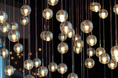 Lighting balls on the chandelier in the lamplight. Light bulbs hanging from the ceiling, lamps on the dark background, selective focus, horizontal Royalty Free Stock Photos