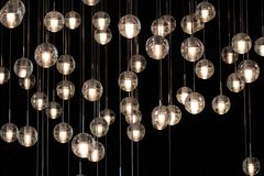 Lighting balls on the chandelier in the lamplight,  light bulbs hanging from the ceiling, lamps on the dark background, selective. Focus, horizontal Stock Photo
