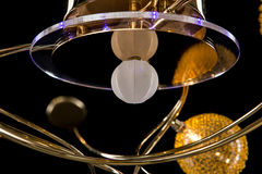 Lighting balls on the golden chandelier in the lamplight, Lamps on the dark background. Close-up Stock Photos