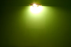 Lighting bulb and blank green wall Royalty Free Stock Photos