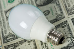 Lighting bulb with money on background Stock Photos