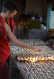 Mcleod Ganj, Dharamsala, India, Tibetan Buddhist monk Lighting Butterlamps. Tibetan Monk lighting Butterlamps in Dharamsala, India Stock Photo