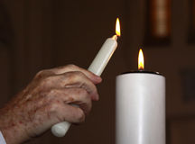 Lighting a candle. A priest lighting a candle as a symbol of love during a baptism ceremony Stock Photos