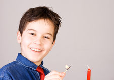 Lighting a candle. Boy lights a candle with match stock image