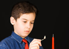 Lighting a candle. Boy lights a candle with match royalty free stock image