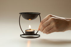 Lighting candle aromatherapy. Hand lighting the candle for an aromatherapy burner Royalty Free Stock Photos