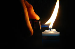 Lighting a candle in dark. Lighting a candle by a lighter stock image
