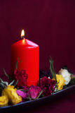 Lighting candle with dry roses Stock Images