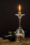 Lighting candle over wine glass Stock Images