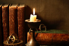 Lighting Candle. Vintage still life with lighting candle near old books Royalty Free Stock Photography