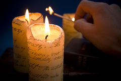Lighting candles. Hand lighting candles scene with holy bible royalty free stock photography