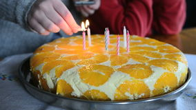 Lighting candles on a birthday cake stock footage