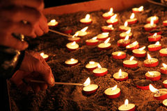 Lighting the candles in the cathedral Stock Photos
