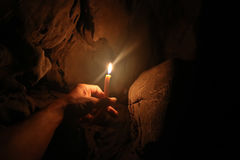 Lighting candles on hand in the limestone caves. Royalty Free Stock Photo