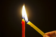 Lighting candles. Hand is lighting two candles against dark background Royalty Free Stock Photo