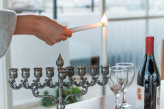 Lighting of candles for Hanukkah holiday. Royalty Free Stock Photography