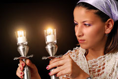 Lighting the candles for Jewish Sabbath. A young woman Lighting the candles for Jewish Sabbath, isolated on black Royalty Free Stock Photography