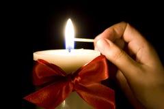 Lighting a Christmas candle stock image