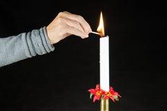 Lighting a christmas candle Stock Photo