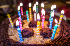 Lighting Colorful candles on birthday cake Royalty Free Stock Images