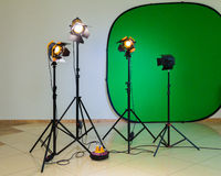 Lighting equipment for filming in the interior. Green background for chromakey. Halogen spotlights with Fresnel lenses. Electrical cables and extension cords Royalty Free Stock Image