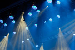 Lighting equipment on the stage of the theatre during the performance. The light rays from the spotlight through the smoke. Blue and yellow rays of light stock photos