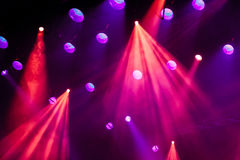 Lighting equipment on the stage of the theatre during the performance. The light rays from the spotlight through the smoke. Red and purple beams stock photos