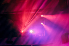Lighting equipment on the stage of the theatre during the performance. The light rays from the spotlight through the smoke. Red and purple beams of light Stock Photo