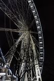 Lighting ferris wheel in the night bottom view. Big attraction in city with bare trees silhouettes foreground. Fun concept. Stock Photo