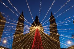 Lighting garland over Christmas tree in Europe royalty free stock photo