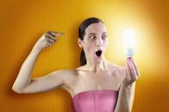 Lighting girl. Nice young girl holding a lighting bulb stock images