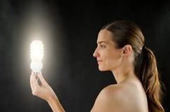 Lighting girl. Nice young girl holding a lighting bulb stock photography