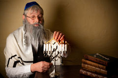 Lighting for hannukah. Old jewish man with beard lighting candles for hannukah Stock Photo