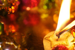 Lighting a Holiday Christmas Candle. Star Candle with decoration and copy space Royalty Free Stock Photo