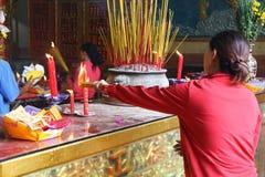 Lighting incense sticks at Buddhist temple Royalty Free Stock Photos