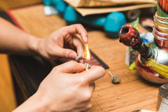 Lighting a Joint. Hands lighting a joint with related cannabis or marijuana smoking items nearby stock images