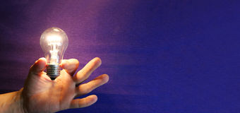 Lighting lamp flashing bulb in human hand on blue background Stock Photography