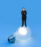 Lighting lamp and man. On blue background royalty free stock photography