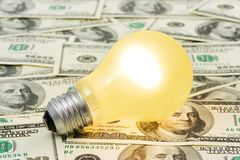 Lighting lamp on money background Stock Images