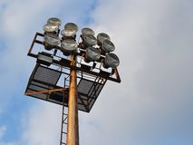 Lighting mast with powerful spotlights over the stadium against the blue sky copy space. Close up royalty free stock photography