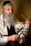 Lighting the menorah. Old jewish man with beard lighting the candles of a menorah Royalty Free Stock Image