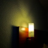 Lighting naturmort. Lighting zigzag tube with red wood and stoned wall in a dark room Stock Photography