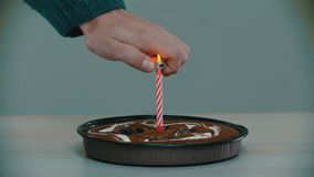 Lighting a pink candle on a cake with a lighter