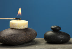 Lighting a small candle on rock. Stock Images
