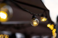 Lighting from small light bulbs in a summer cafe stock images