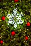 Lighting snow flake on a Christmas tree. Royalty Free Stock Photos