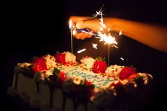 Lighting sparkles on a birthday cake. Lighting sparkles on top of a birthday cake with strawberries Stock Images