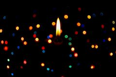 Lighting star candle. Background black and a candle is burning royalty free stock photography