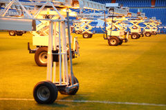 Lighting system for growing grass at football stadium. Lighting system for growing grass at empty football stadium with blue seats Royalty Free Stock Image