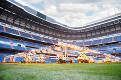 Lighting system for growing grass and lawn at stadium. Lighting system for growing grass and lawn at empty outdoor football stadium with blue seats Stock Images